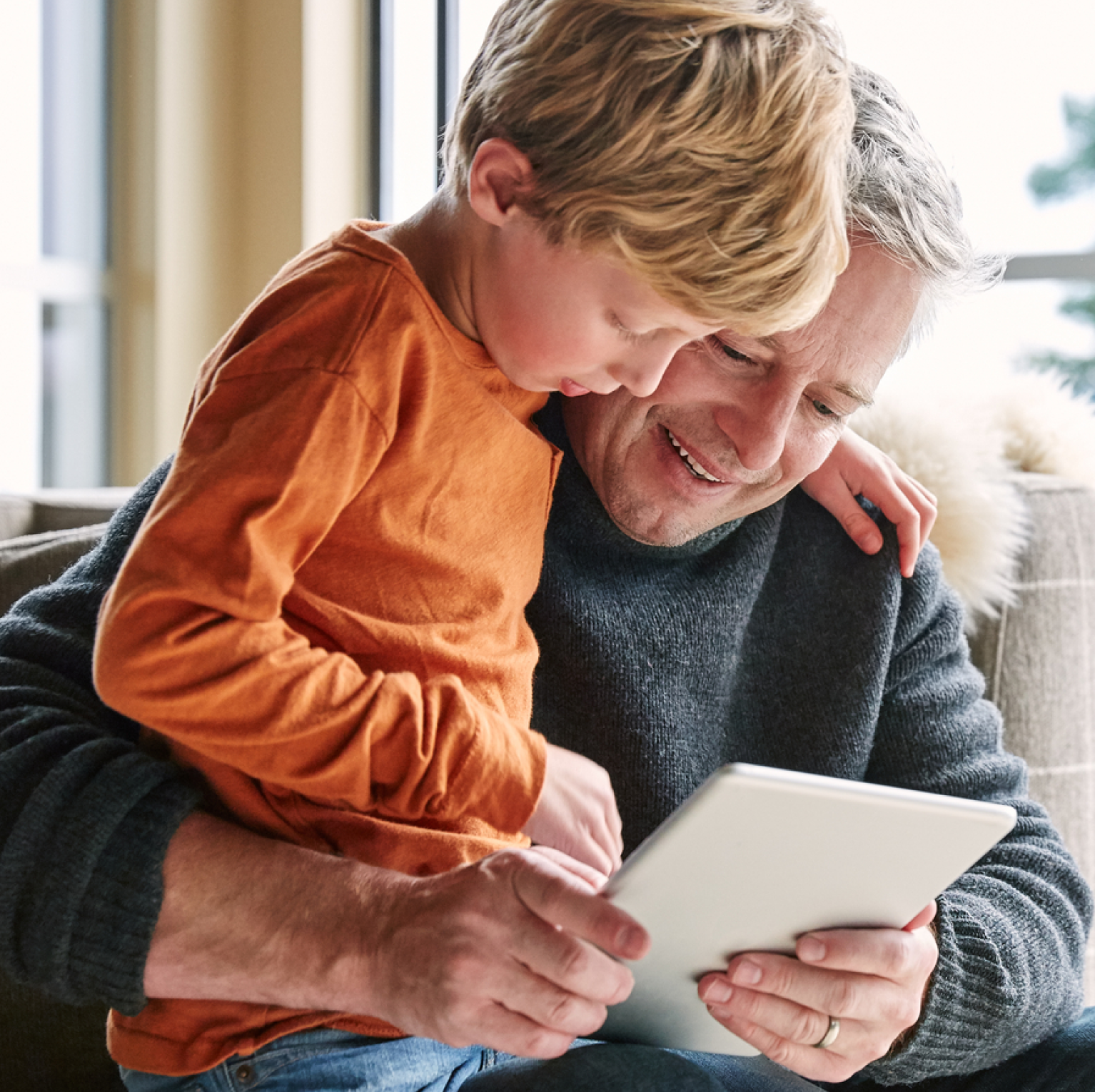 Photo of a man and young boy looking attentively at an iPad